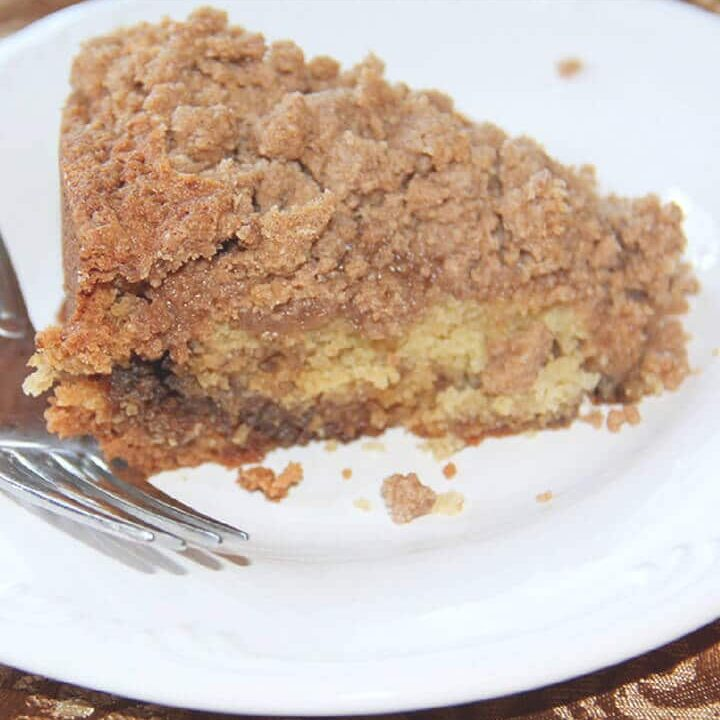 A slice of sour cream coffee cake on a white plate.