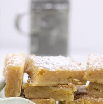 Chess squares stacked on a plate with powdered sugar on top.