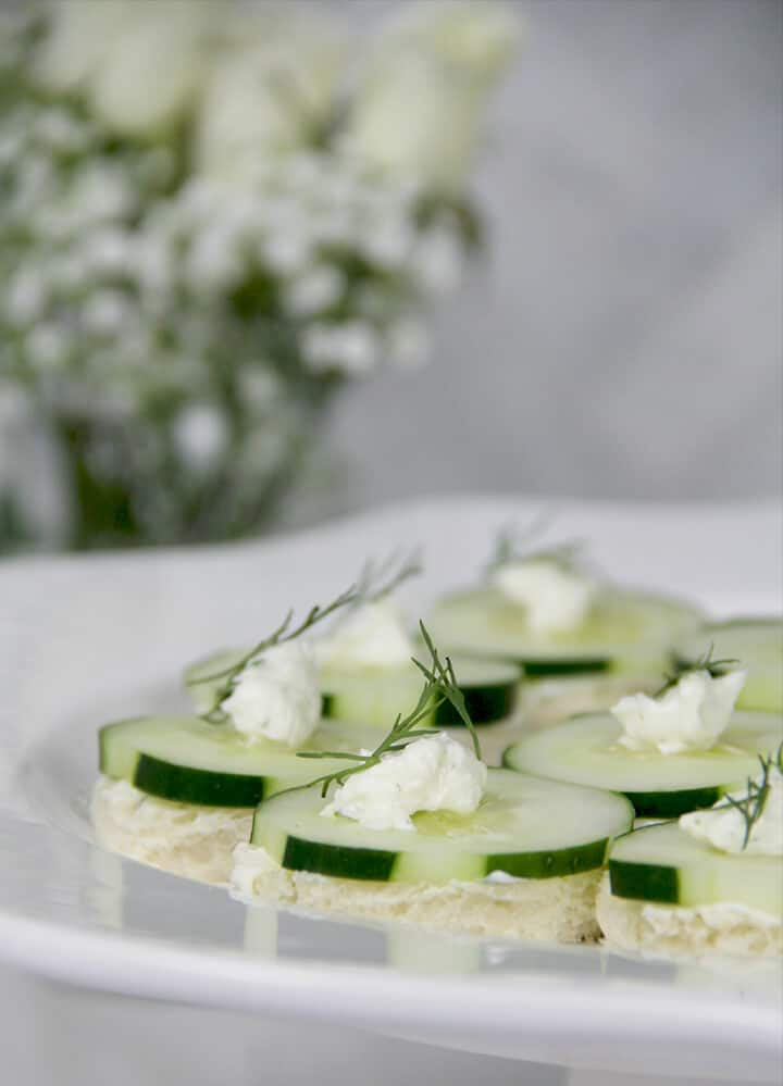 Photo of a platter of cucumber sandwiches with a vase of flowers in the background.