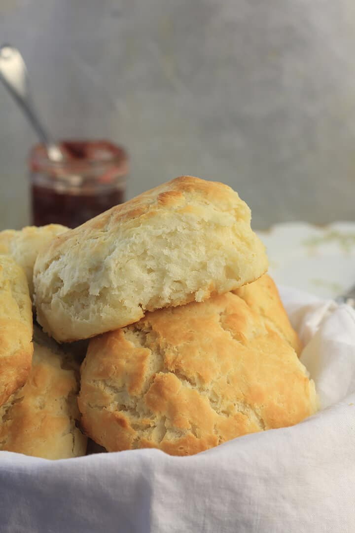 Basket of biscuits with jam and plates.