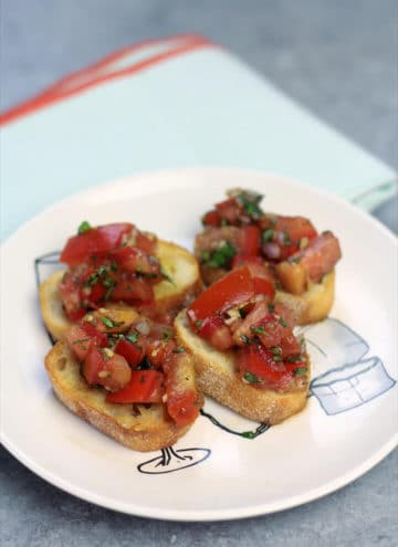 Bruschetta on toasted bread on a plate.
