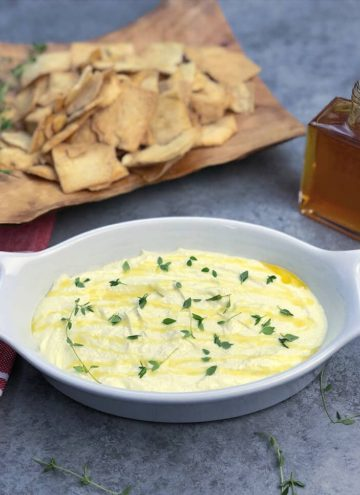 White bowl of whipped feta dip with honey and chips in the background.