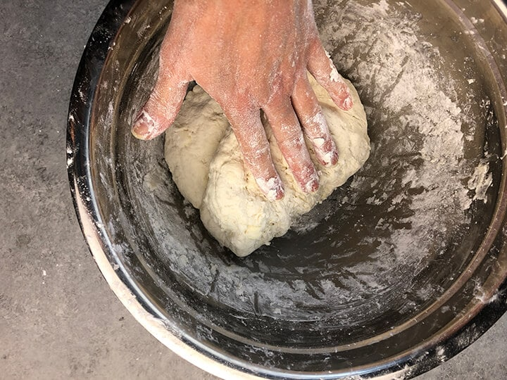A hand kneading biscuit dough in a stainless bowl.