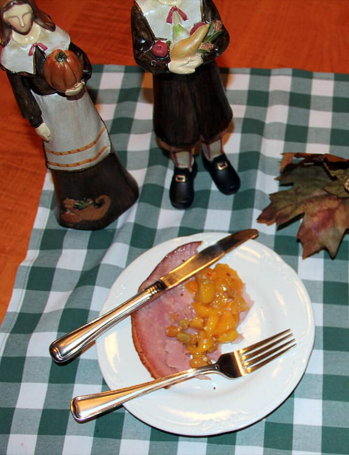 Slice of ham with peach chutney on a white plate with a knife and fork.