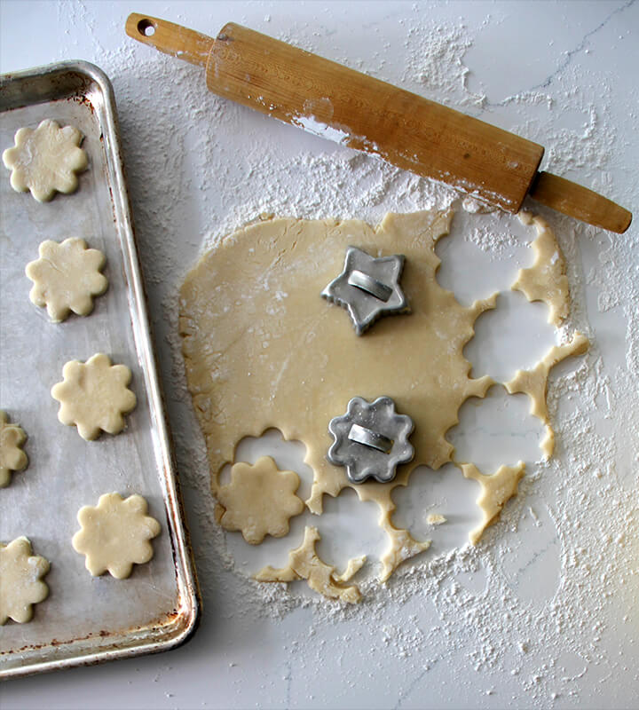 cookie cutters and rolling pin cutting tea cakes dough.