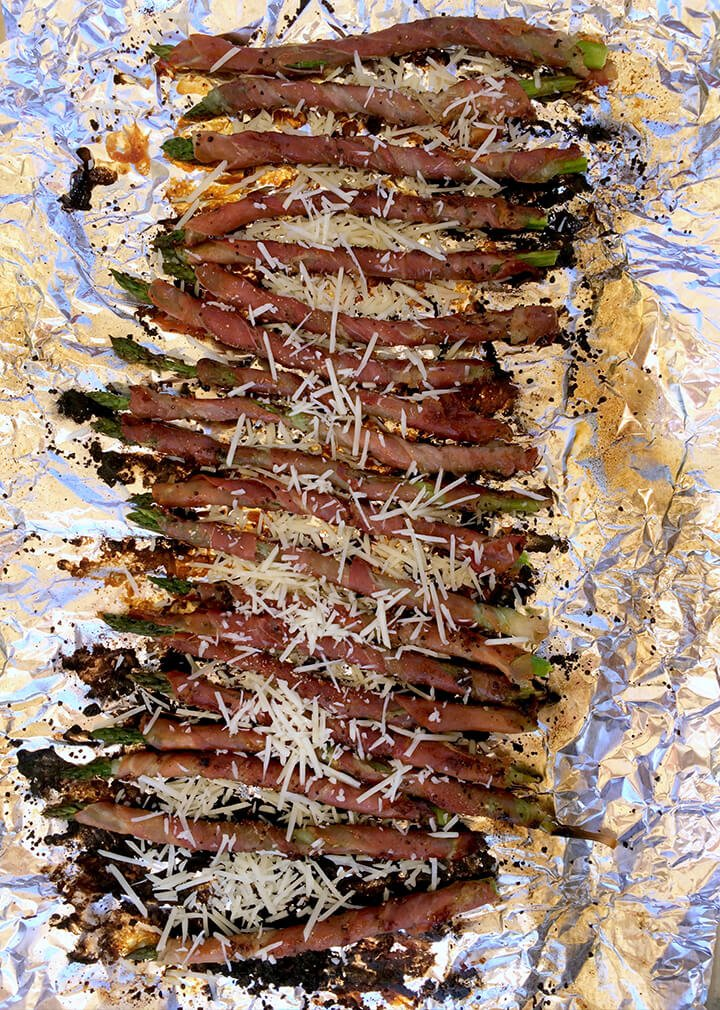 A foil covered tray of prosciutto wrapped asparagus with parmesan.