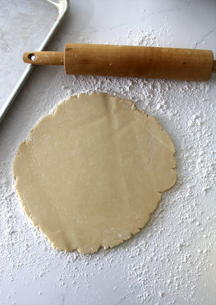 Southern tea cakes dough rolled out on the counter next to a rolling pin.