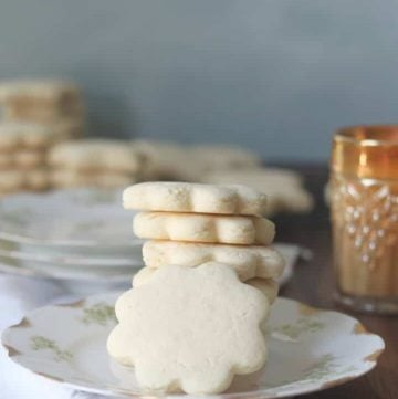Tea cakes stacked on a plate with a glass of milk.