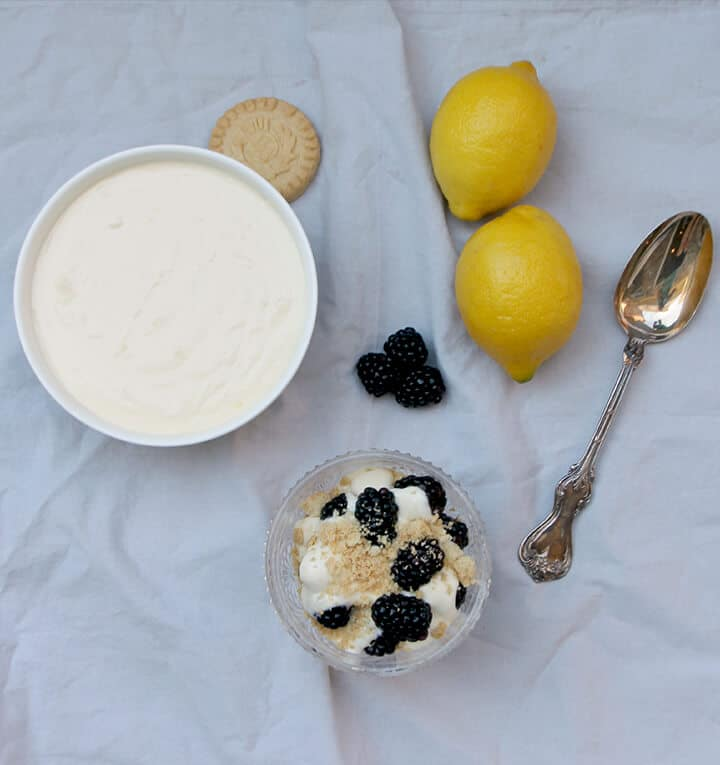 Overhead photo of a bowl of lemon cream cheese with lemons and berries.