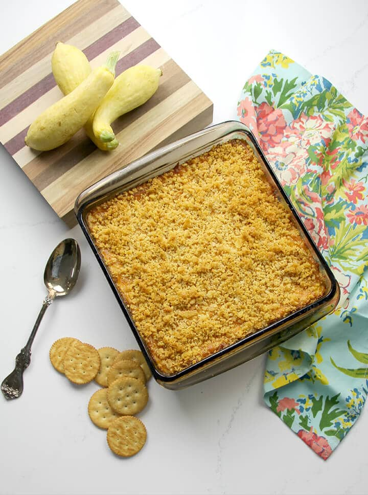 A full dish of baked squash casserole with Ritz crackers and a spoon on the side.
