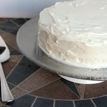A cake on a glass platter frosted with easy buttercream frosting.