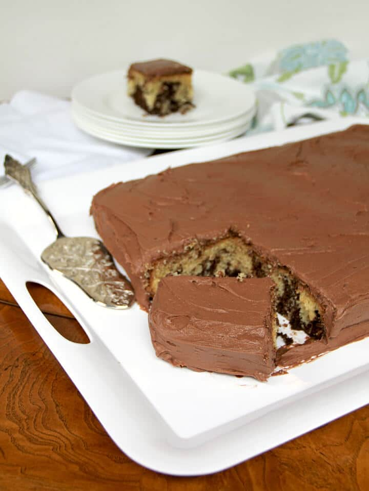 A cake frosted with best chocolate buttercream frosting on a white platter.