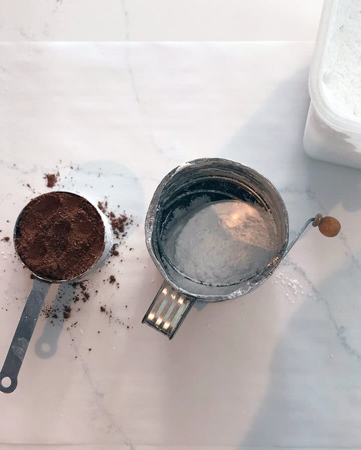A cup of cocoa beside a sifter of powdered sugar.