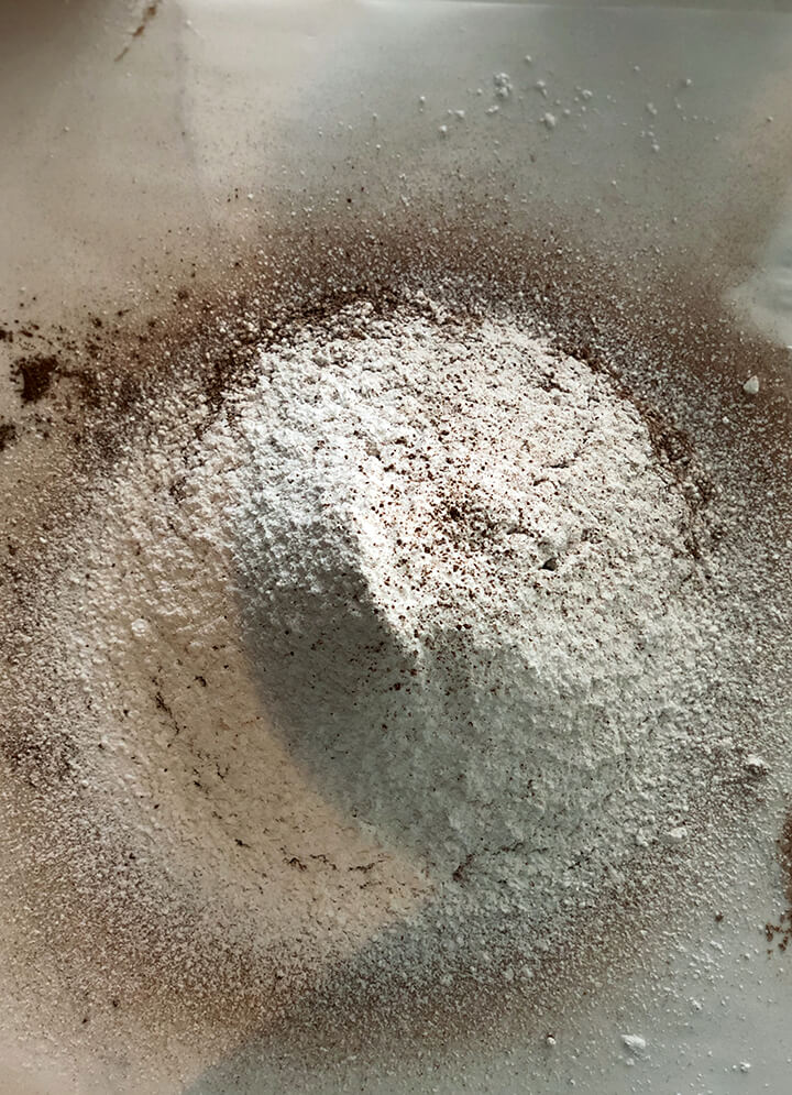 Powdered sugar and cocoa sifted to make chocolate buttercream frosting.