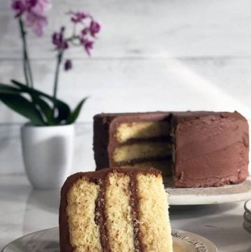 A slice of moist yellow cake on a plate with the whole cake in the background with chocolate frosting.