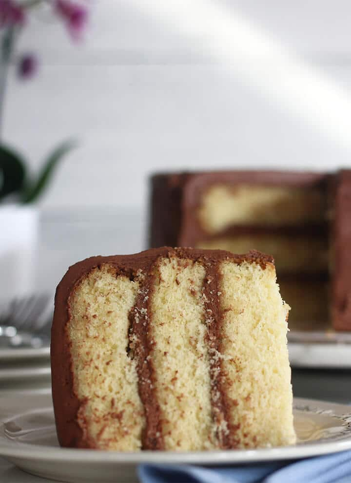 A slice of yellow cake on a plate with chocolate frosting and a cake in the background.