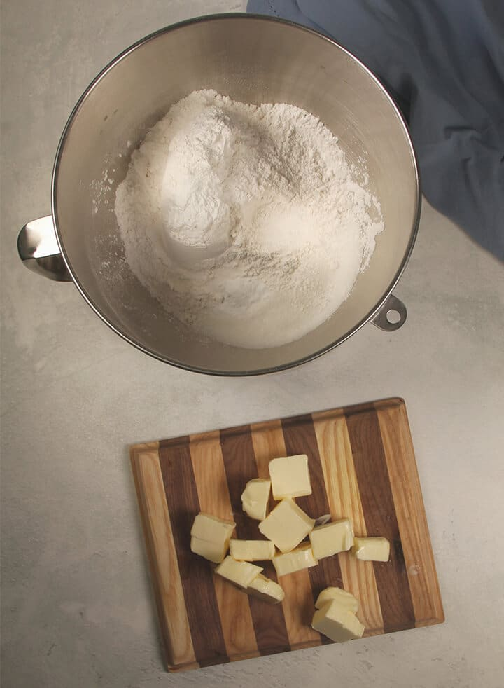 Diced butter on a cutting board and a bowl of flour for making homemade yellow cake.