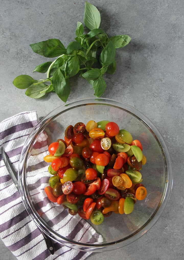 Bowl of halved cherry tomatoes with basil on the counter.