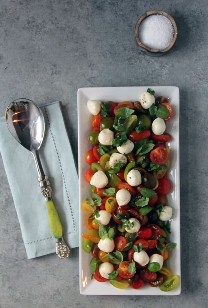 Caprese salad cherry tomatoes on a white platter next to a blue napkin with a serving spoon.