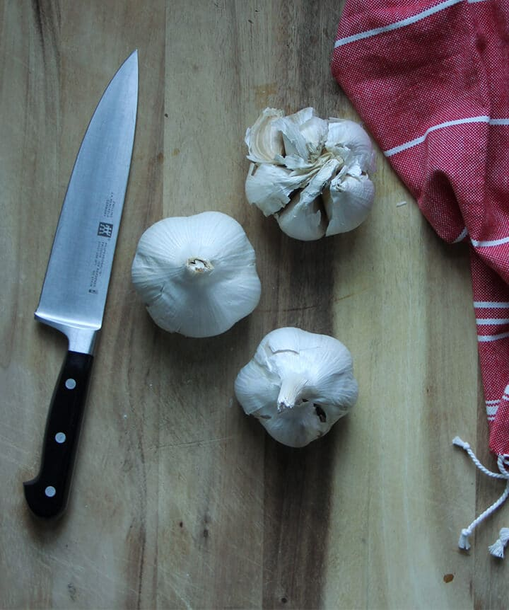 Three heads of garlic on a cutting board with a knife.
