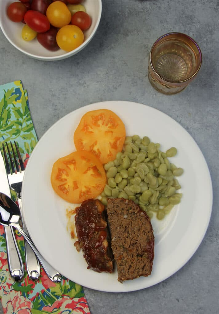 A white plate featuring Southern meatloaf recipe baked meatloaf with butterbeans and tomatoes.