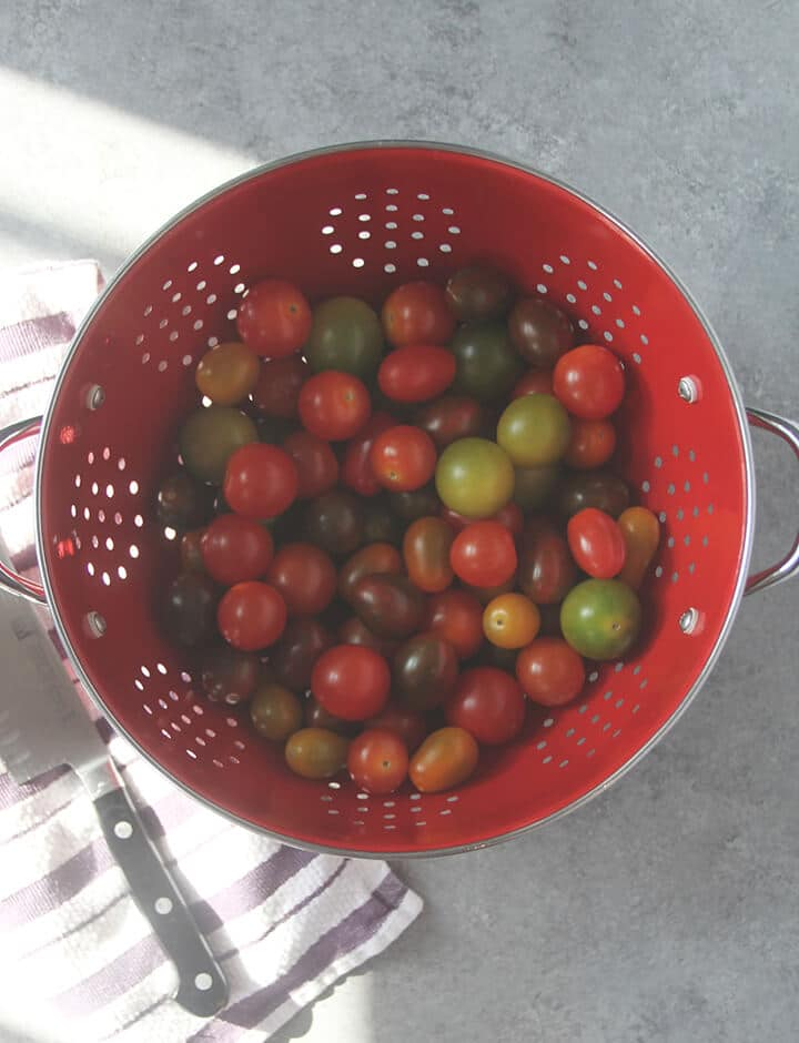 A strainer with cherry tomatoes ready to cut in half.