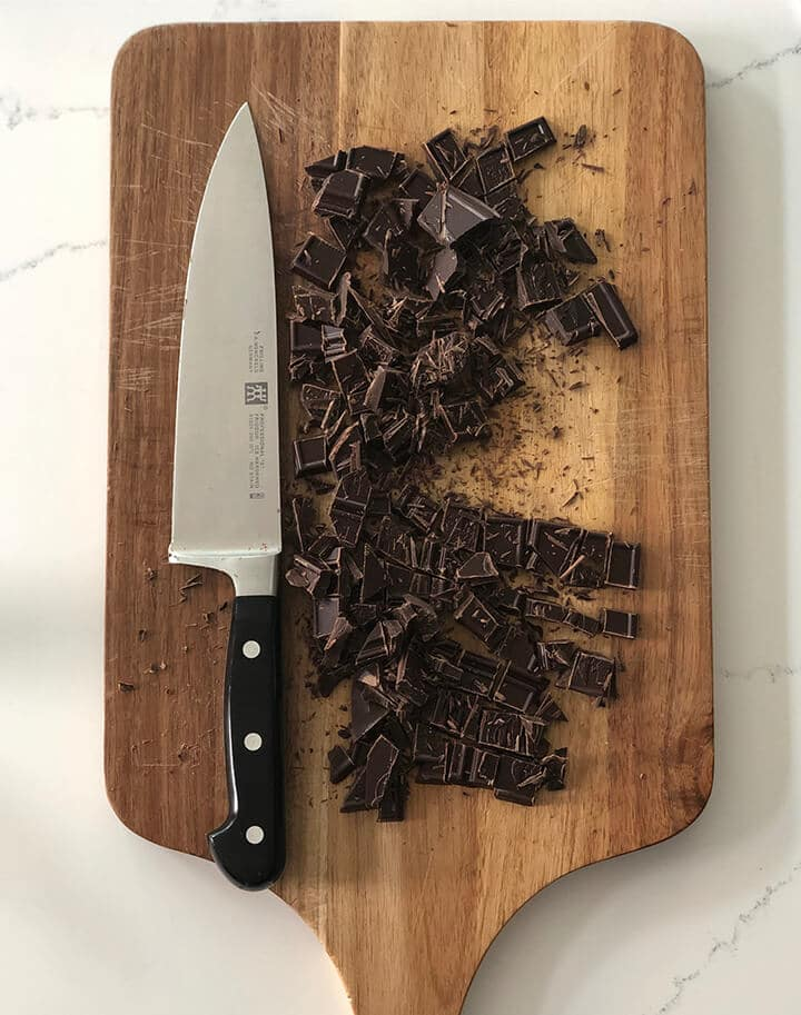 Chopped bittersweet chocolate and a knife on a cutting board.