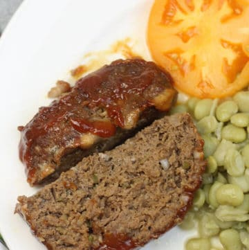 A closeup of meatloaf on a white plate with butterbeans and tomatoes.
