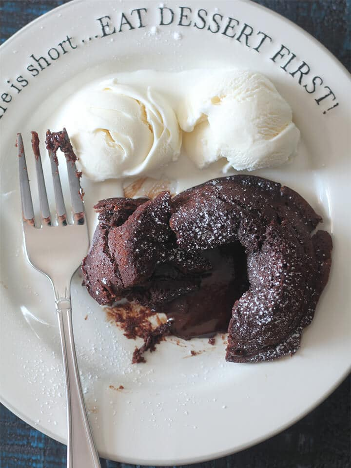 Overhead photo of chocolate lava cake on a plate with vanilla ice cream and a fork.
