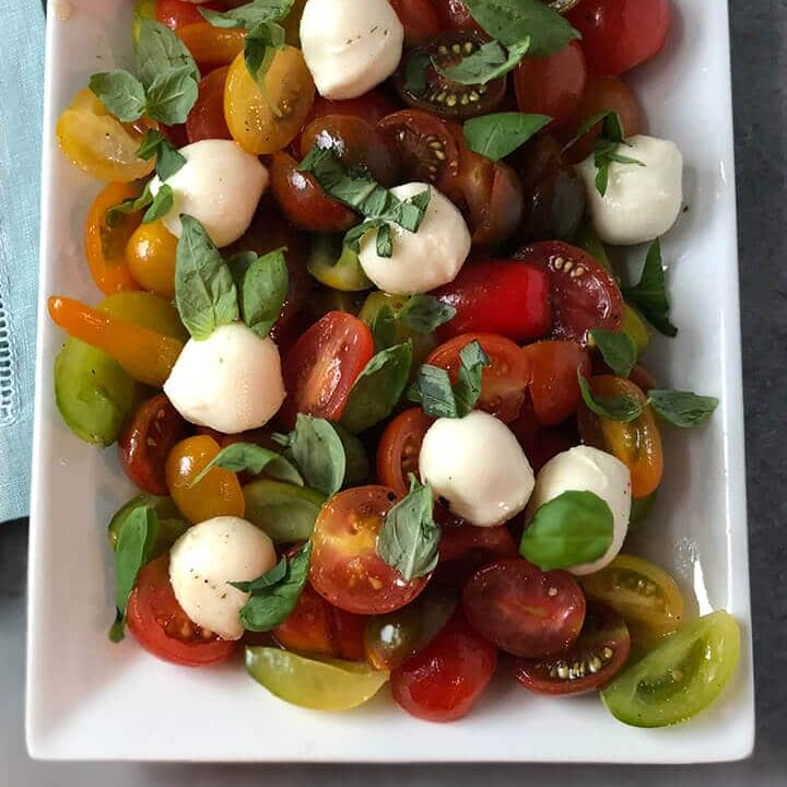 Cherry Tomato Salad with basil on a white platter.