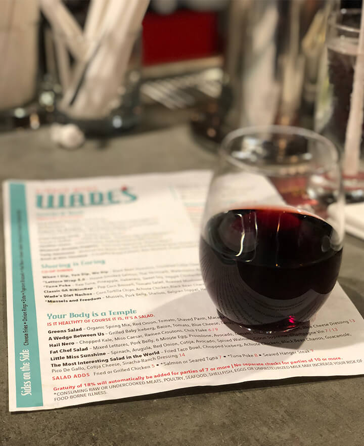 A glass of red wine atop the menu on the bar counter at Wade's in Smyrna.