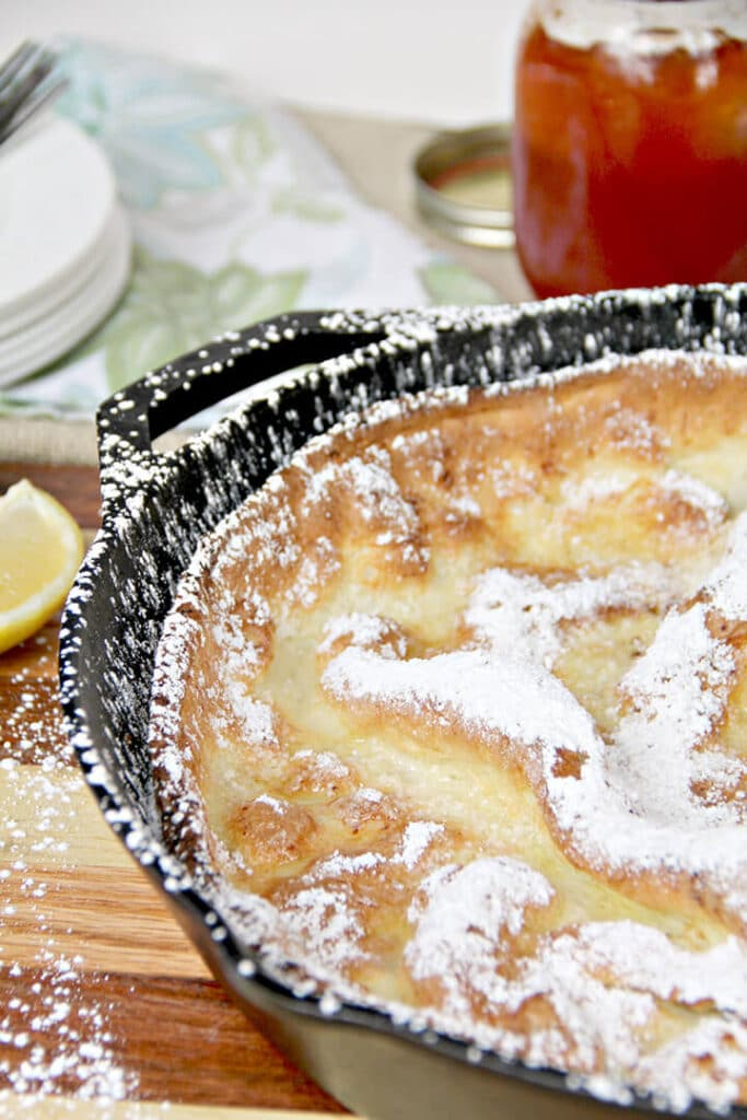 Side view of a Dutch baby pancake in a cast iron skillet dusted with powdered sugar.