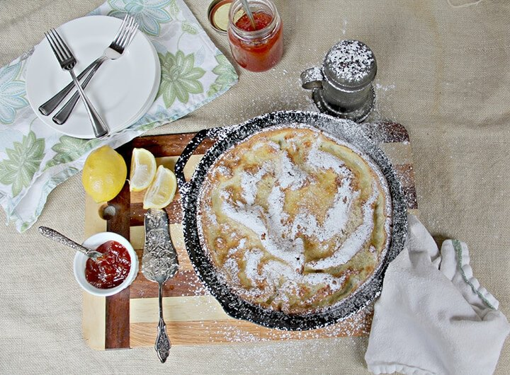 Overhead photo of a skillet of Dutch baby german pancake with plates, lemons, and jelly on the side.