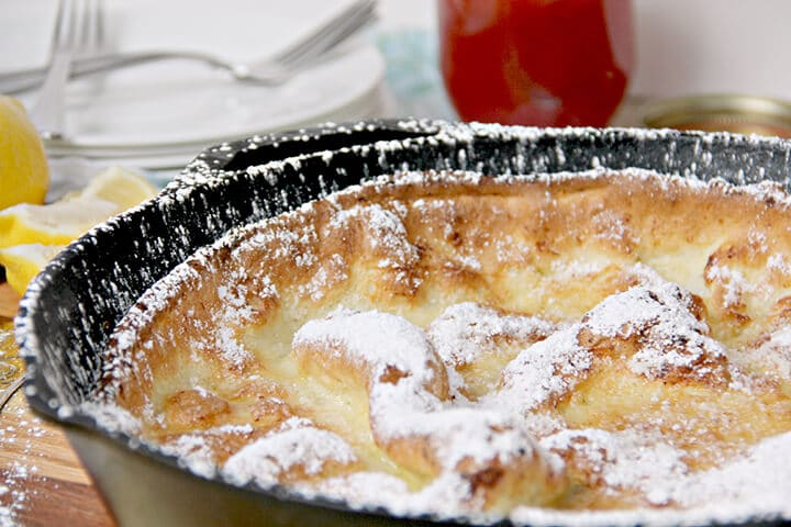 Side view of dutch baby pancake with powdered sugar in a cast iron skillet.