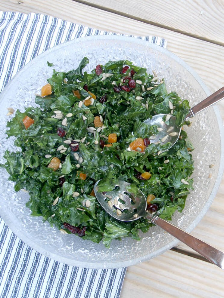 Overhead of a bowl of a salad with salad tongs.