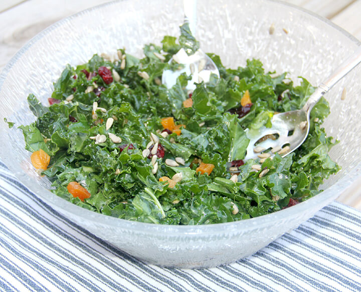 Side view of a bowl of easy kale salad on a table with a blue and white towel.