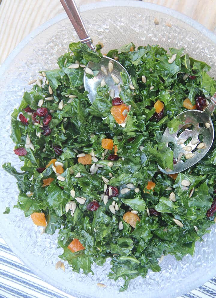 Easy kale salad in a bowl with salad tongs over a blue and white towel.