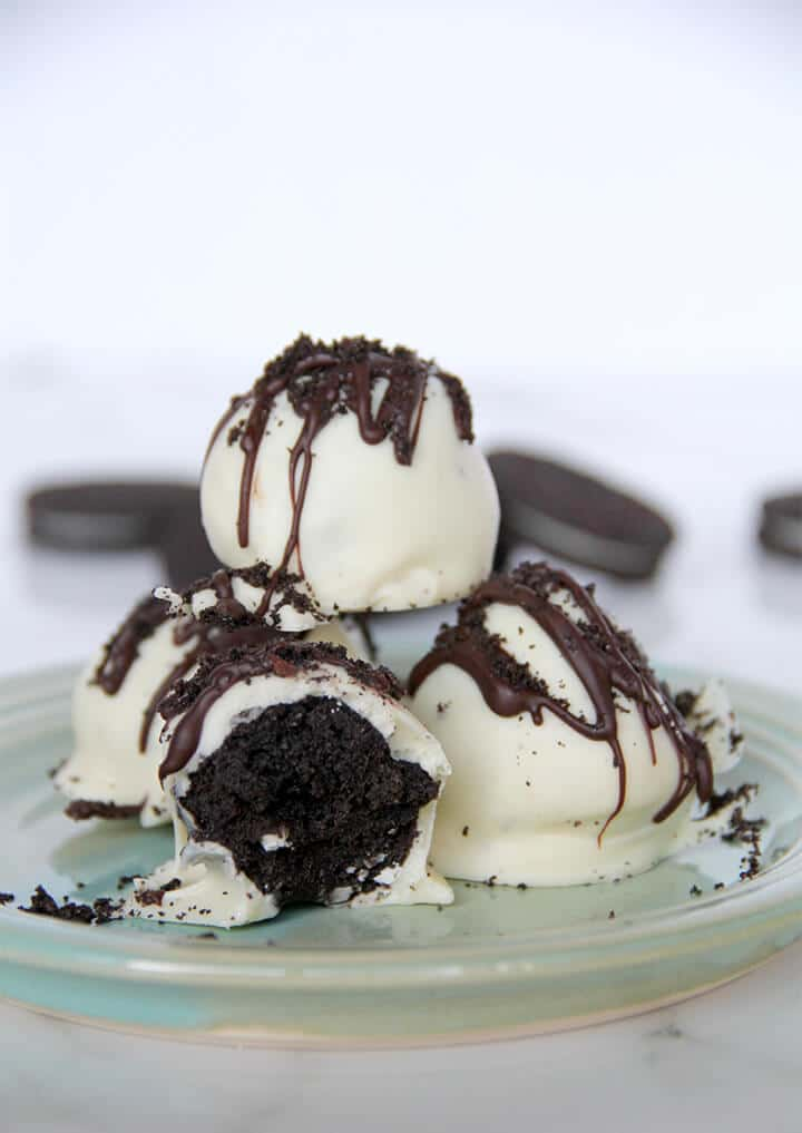 White chocolate covered oreo balls stacked on a plate.