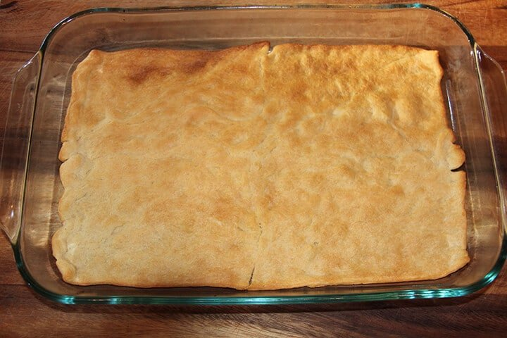 Baked crescent roll crust in a dish.
