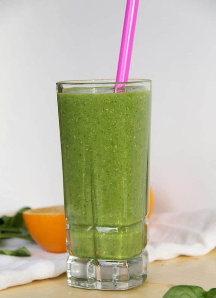 A glass of super green smoothie with a pink straw and an orange on a cutting board.