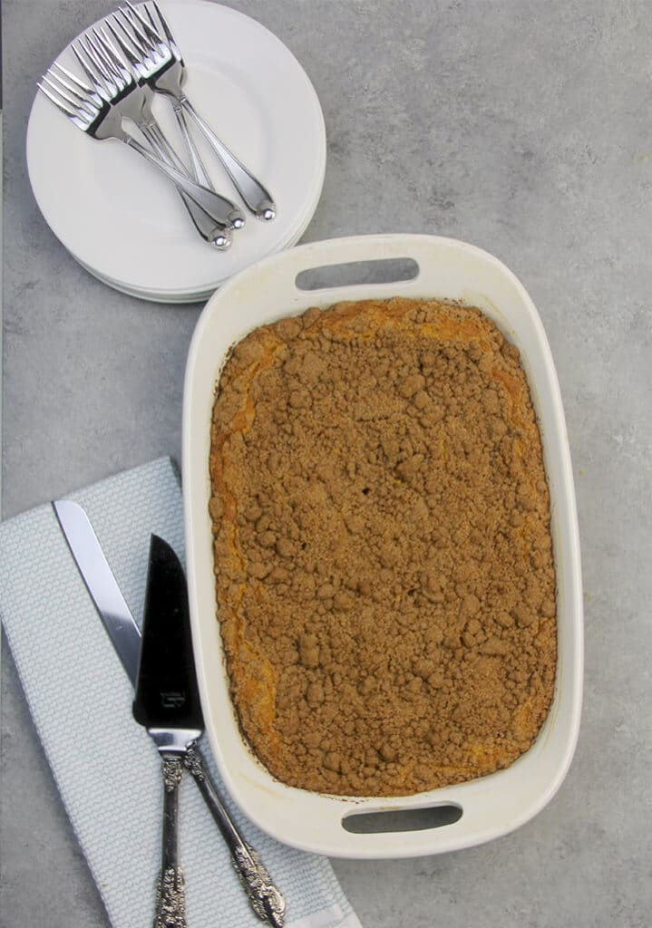 Baked whole pumpkin crumb cake with cake servers on a towel.