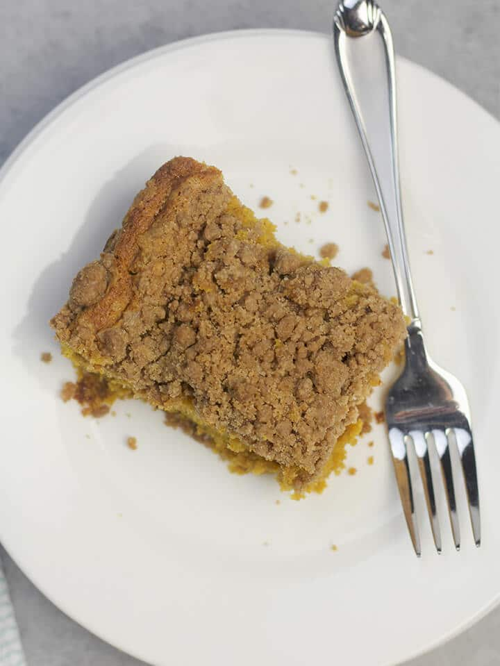 Overhead view of a piece of pumpkin crumb cake on a white plate with a fork.