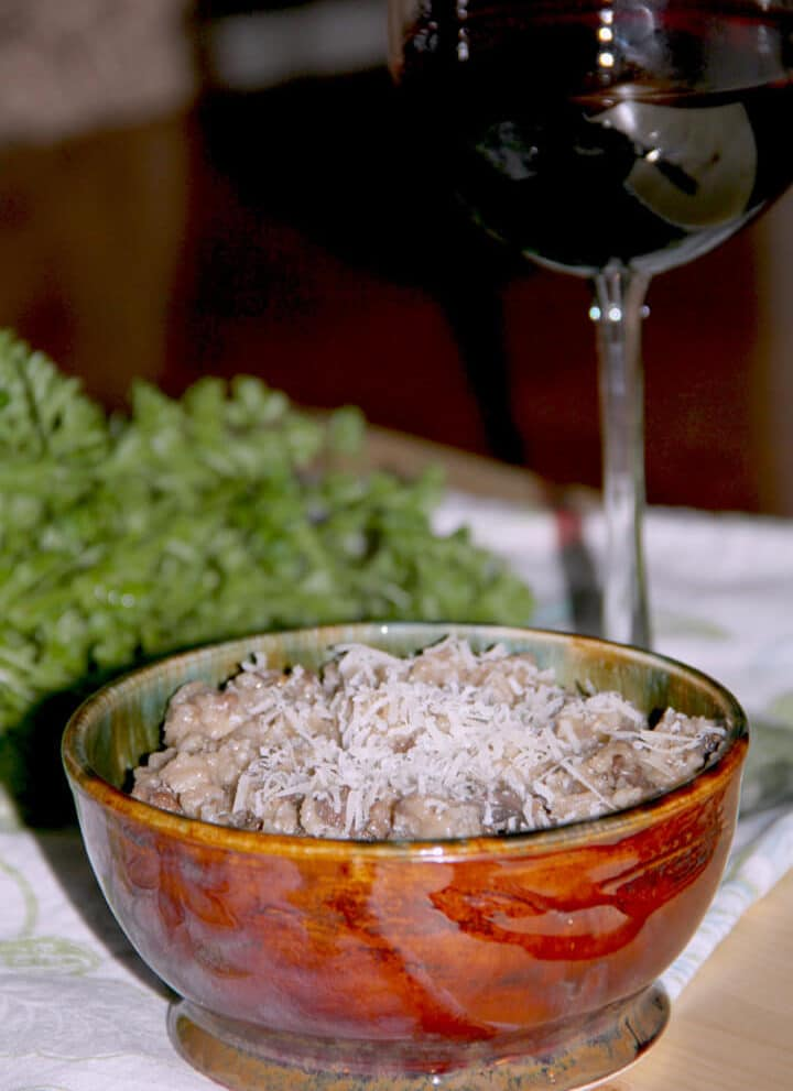 A bowl of sausage risotto with a glass of wine in the background.
