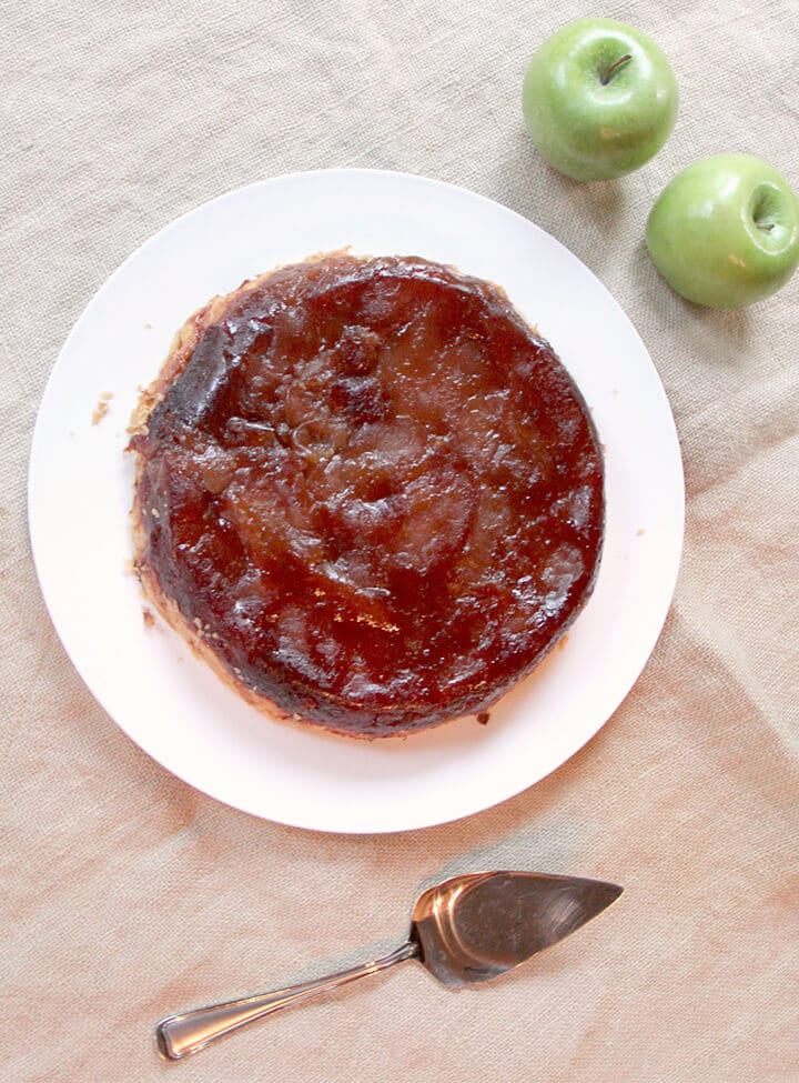 Overhead photo of apple tarte tatin on a plate with a server next to it.