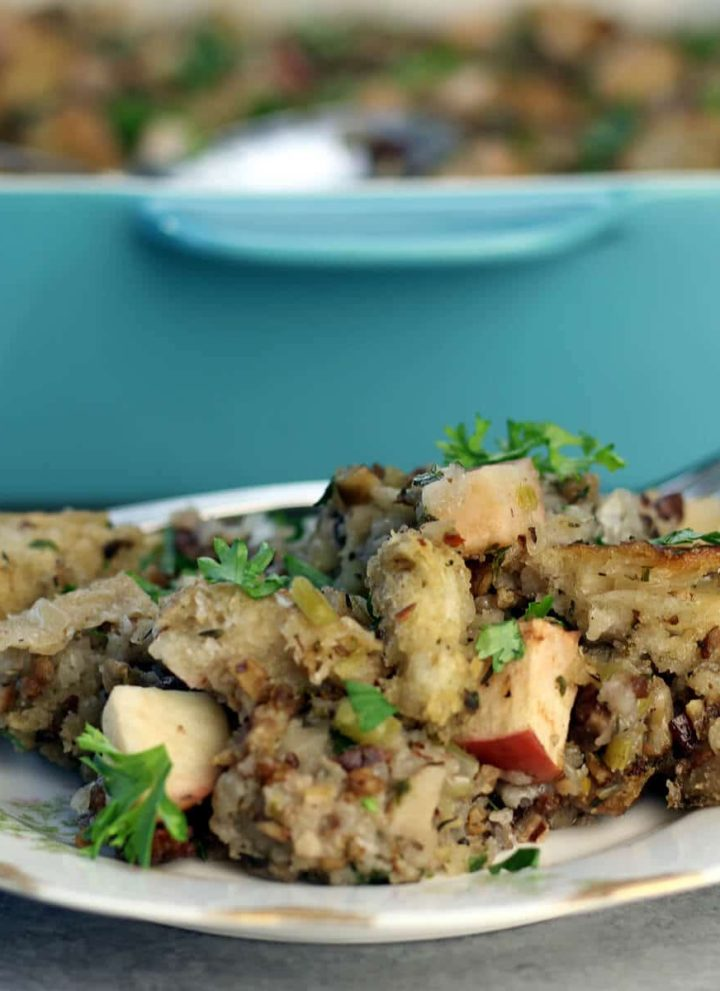 A serving of apple sausage stuffing on a plate with the dish in the background.