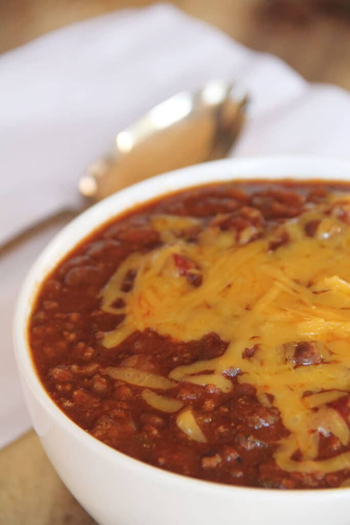A white bowl of classic beef chili topped with grated cheese with a spoon on the side.