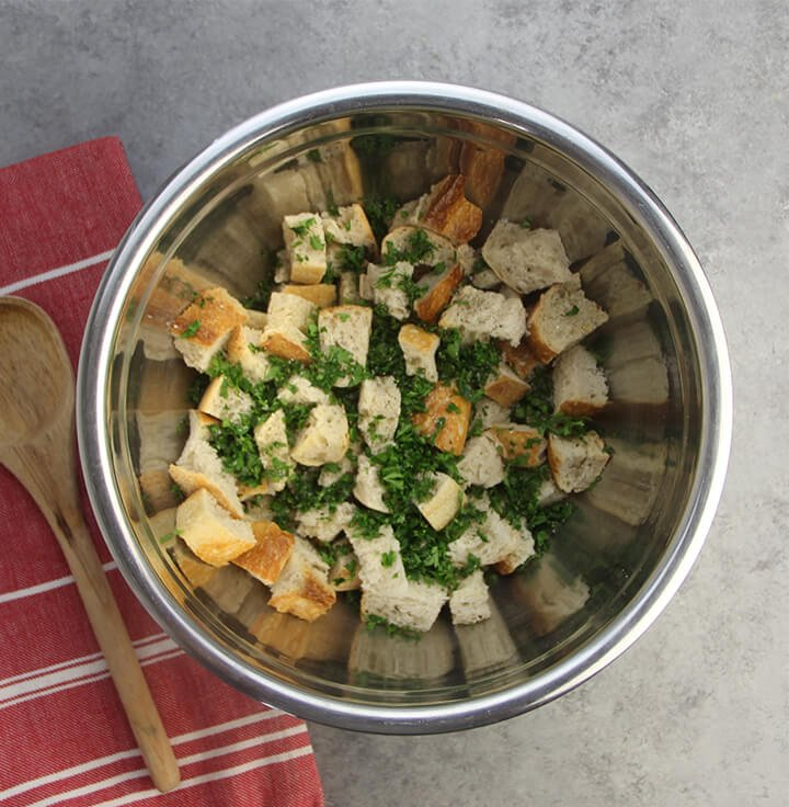 Bread cubes in a bowl with fresh herbs mixed in.
