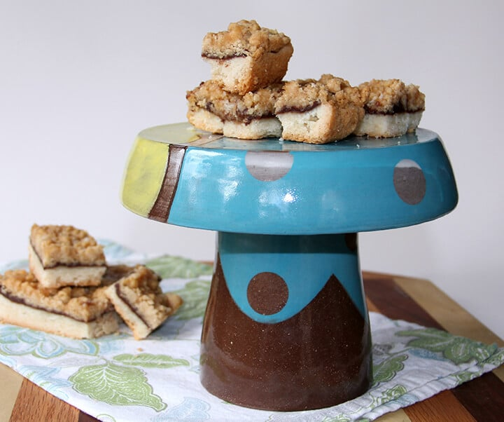 Chocolate caramel shortbread bars baked and sitting on a cake stand.