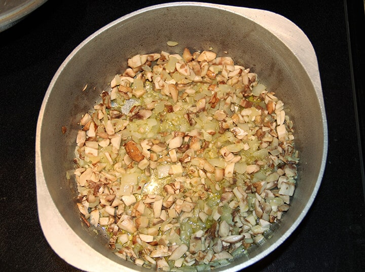 A pot with onions and mushrooms cooking.