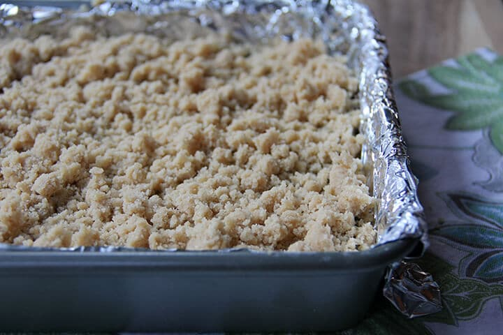 Streusel over shortbread in a baking pan.